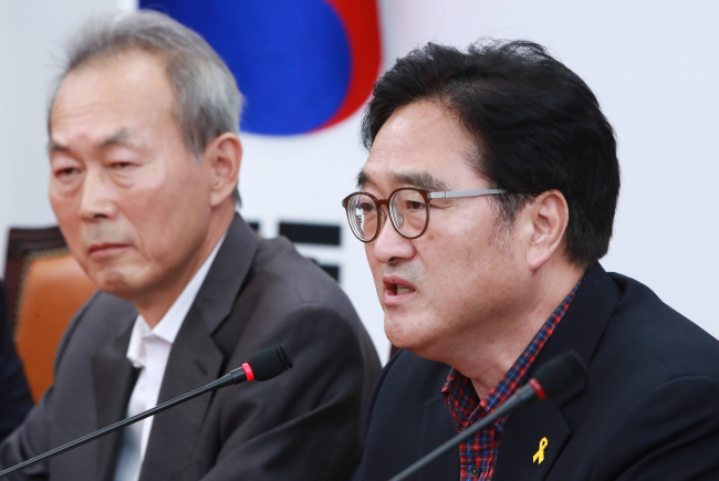 The ruling Democratic Party of Korea's floor leader Rep. Woo Won-shik (right) speaks at a meeting on the 2014 Sewol ferry disaster at the National Assembly on Sunday. Yonhap