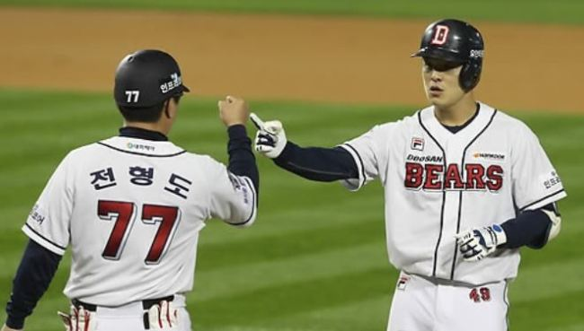 Min Byung-hun of the Doosan Bears (R) celebrates with his first base coach Jeon Hyung-do after a base hit in the bottom of the first in Game 1 of the Korea Baseball Organization postseason series against the NC Dinos at Jamsil Stadium in Seoul on Oct. 17, 2017. (Yonhap)