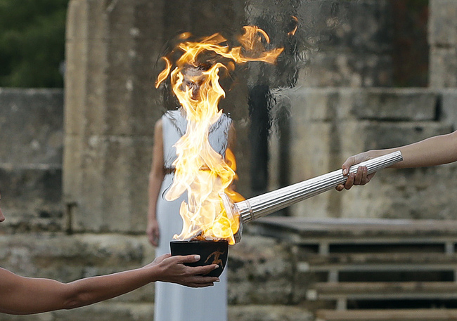Actress Katerina Lehou, right, as high priestess, lights the torch during the lighting ceremony of the Olympic flame in Ancient Olympia, southwestern Greece, on Tuesday, Oct. 24, 2017. The flame will be transported by torch relay to Pyeongchang, South Korea, which will host the Feb. 9-25, 2018 Winter Olympics. (AP-Yonhap)