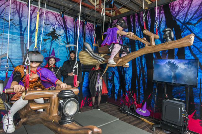 Visitors board the flying broom ride wearing virtual reality headsets at Haunted House in the Everland amusement park in Yongin, Gyeonggi Province. (Everland)