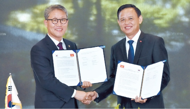 Korea Forest Service Minister Kim Jae-hyun (left) shakes hands with Vietnam's Vice Minister for Agriculture and Rural Development Ha Cong Tuan after agreeing on cooperation in investment, joint research and preserving seeds for forests at the ninth Korea-Viet Nam Forest Cooperative Committee held on the sidelines of the APEC meeting of ministers responsible for forestry in Seoul on Tuesday. (KFS)