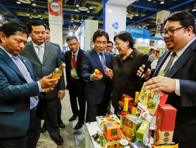 Kim Young-sun (center), secretary-general of the ASEAN-Korea Center and Korea's former ambassador to Indonesia, examines food products at the ASEAN Trade Fair 2017 at Coex in Seoul. In the photo are Malaysian Ambassador Rohana Ramli (second from right), Indonesian Ambassador Umar Hadi (second left) and Myanmar Ambassador Thura Thet Oo Maung (left). (ASEAN-Korea Center)