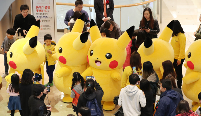 "PIKACHU PARADE -- Several people dressed as ""Pokemon"" character Pikachu parade at the Pokemon Festa in Jamsil, Seoul, on Sunday. The festival at Lotte World Tower began on Saturday and runs through Nov. 12. (Yonhap)"