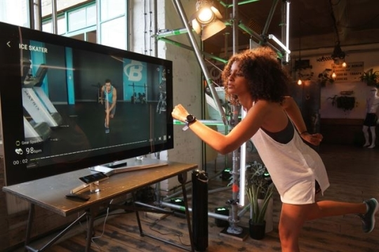 A user works out with the Samsung Gear Sport through a fitness program connected to a TV. (Samsung Electronics)