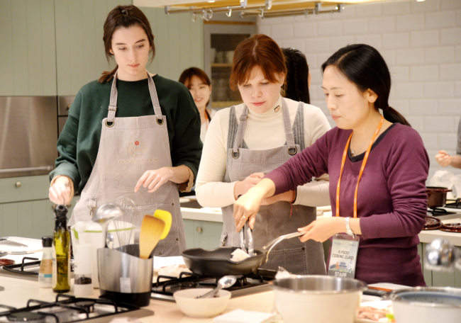 Tourists participate in the Hallyu K-Food Cooking Class, run by the Seoul Metropolitan Government, at the CJ Cheil Jedang cooking studio in Jung-gu, Seoul, Thursday. (Park Hyun-koo/The Korea Herald)