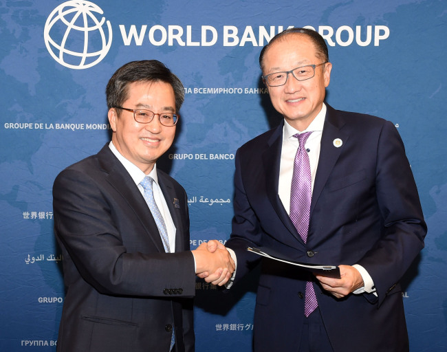 World Bank President Jim Yong Kim (right) and Korean Finance Minister Kim Dong-yeon pose after signing a memorandum of understanding to expand the capacity of the World Bank Group Korea Office in Songdo, Incheon on Oct. 14. (Yonhap)