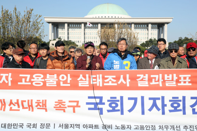 Members of civic groups advocating the rights of security guards hold a press conference in front of the National Assembly in Seoul on Wednesday. (Yonhap)