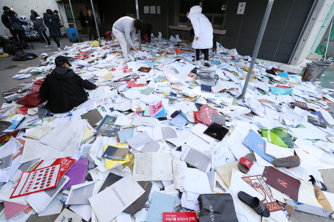 Students rummage through a pile of study aids discarded to mark the end of their preparations in Seoul on Thursday. Yonhap