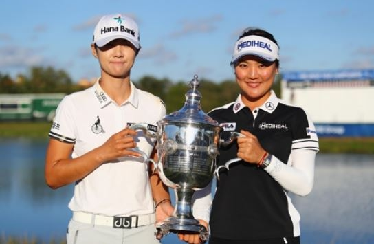 In this photo provided by the LPGA Tour, South Korean players Park Sung-hyun (L) and Ryu So-yeon hold the trophy for the Player of the Year after the conclusion of the CME Group Tour Championship in Naples, Florida, on Nov. 19, 2017. (Yonhap)