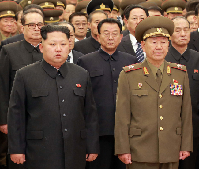 Hwang Pyong-so(right)stands with North Korea leader Kim Jong-un. Yonhap