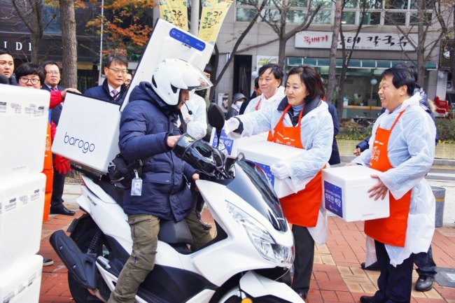 KIMCHI DELIVERYTO THE POOR– Rep. Park Young-sun of the ruling Democratic Party of Korea (second from right) and Guro-gu Mayor Lee Sung (right)load kimchiand fresh eggs onto motorcycles operated by Korean food and goods delivery service provider Barogo in Seoul, Wednesday. The startup delivered 670 plates of eggs and 1,180 kimchi cabbages donated by the Kookmin Ilbo to underprivileged households and social service centers in Guro-gu as part of its seasonal charity program. (Courtesy of Barogo)