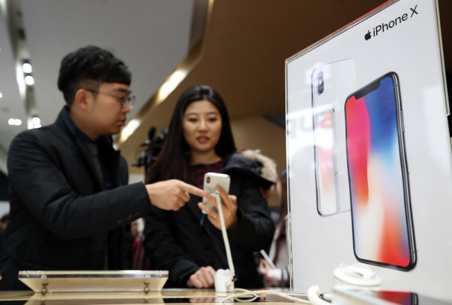 IPHONE X IN SEOUL -- Customers check out the iPhone X at the KT Square in Gwanghwamun of Seoul, Friday. The iPhone X, which Apple designed as its 10th anniversary smartphone, officially became available for purchase through Korea's three mobile carriers SK Telecom, KT and LG Uplus on the day. (Yonhap)