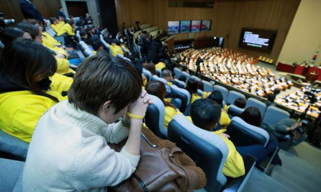 Family members of the Sewol ferry sinking victims watch from the National Assembly`s main chamber as the parliament holds a final vote on a bill that calls for reinvestigations of major disasters, including the 2014 ferry sinking.(Yonhap)