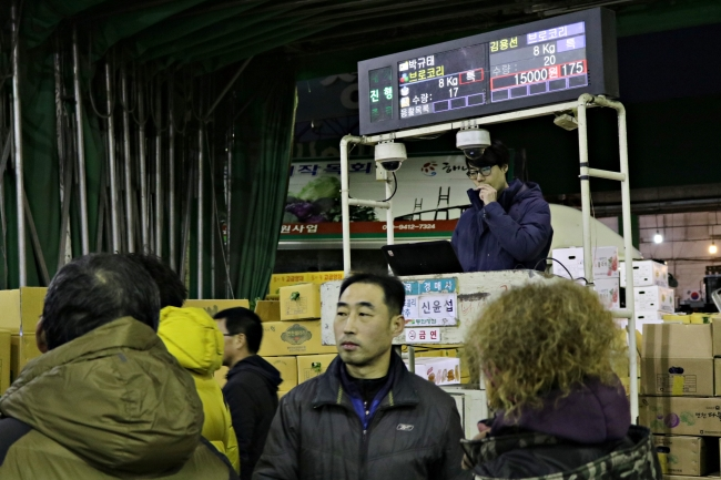 An auctioneer stands at a podium in front of bidders at Garak Wholesale Market in Seoul. (Son Ji-hyoung/The Korea Herald)