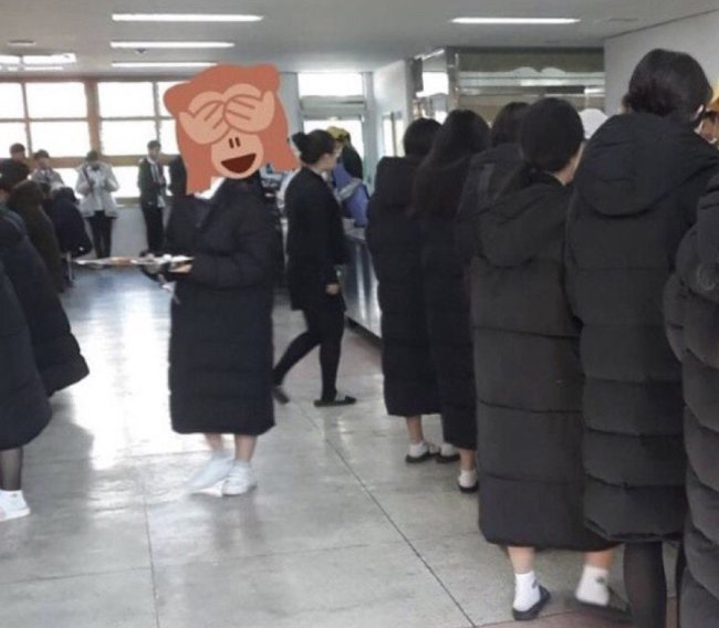 A group of students wearing long padded coats at school.