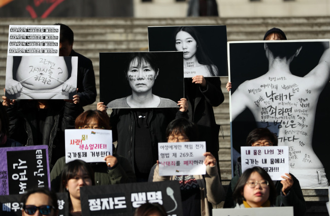 Pro-choice activists hold up banners and images of female bodies carrying messages in favor of their right to self-determination at a protest in central Seoul on Nov. 9. Yonhap