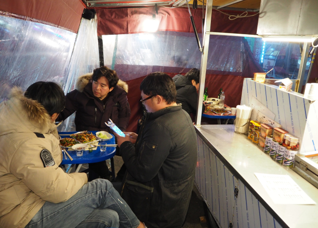 Korean men in their 40s — many who remember their old days at pojangmacha — enjoy an evening of soju and food inside a pojangmacha in northern Seoul. (Joel Lee/The Korea Herald)