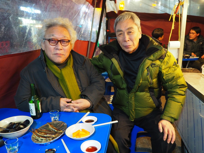 Dono Kim (right) and his friend of over 60 years at a pojangmacha in northern Seoul (Joel Lee/The Korea Herald)