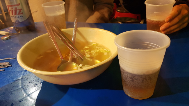 Each table is given a free steaming bowl of broth at most pojangmacha. (Rumy Doo/The Korea Herald)