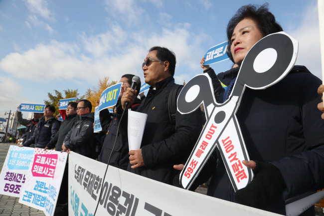 "A group calling for the revision of labor laws for fairer working conditions holds a rally outside the National Assembly on Nov. 15. A picket reads ""over-work death out,"" referring to deaths allegedly caused by the physical strain brought on by excessive work. Yonhap"