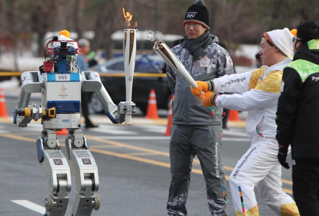 HUMANOID ROBOT CARRIES OLYMPICS TORCH — Hubo, a humanoid robot developed by a team of researchers ledby Professor Oh Jun-hoat Korea's top science and technology research university KAIST, receives the 2018 PyeongChang Olympics torch from Dennis Hong, the founding director of the Robotics and Mechanisms Laboratoryat UCLA, in Daejeon, Monday. It is the first time that a robot has carried the Olympic torch. (Yonhap)
