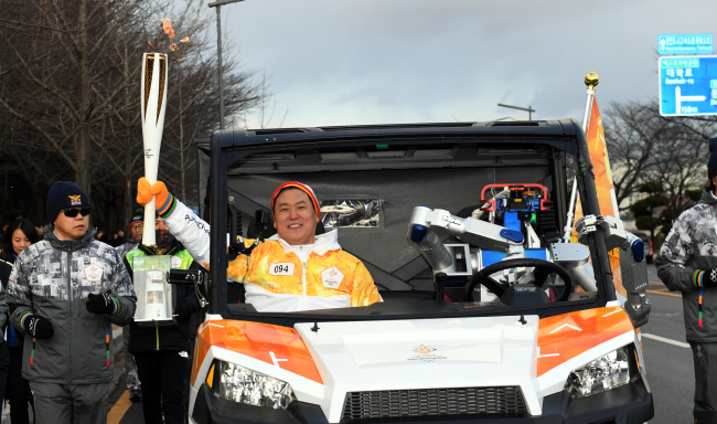 HUMANOID ROBOT CARRIES OLYMPICS TORCH — Hubo, a humanoid robot developed by a team of researchers at Korea's top science and technology research university KAIST, sits in the driver seat of a self-drivingvehicle accompanied by Professor Dennis Hong, who is carrying the 2017 PyeongChang Olympics torch, in Daejeon, Monday. (Yonhap)