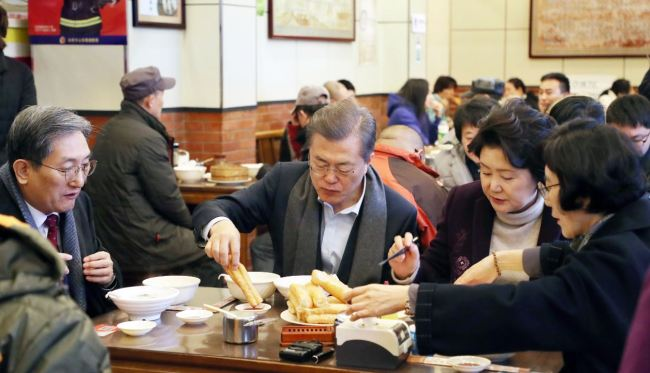 President Moon Jae-in (center) and First Lady Kim Jung-sook (Right) kicked off the second day of state visit to China with breakfast at a streetside restaurant in Beijing early Thursday.