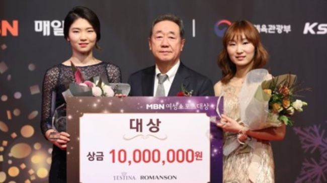 South Korean short track speed skaters Shim Suk-hee (L) and Choi Min-jeong (R) pose for a photo with Maekyung Media Group Chairman Chang Dae-whan after they won the grand prize at the MBM Women Sports Awards in Seoul on Dec. 14, 2017. (Yonhap)