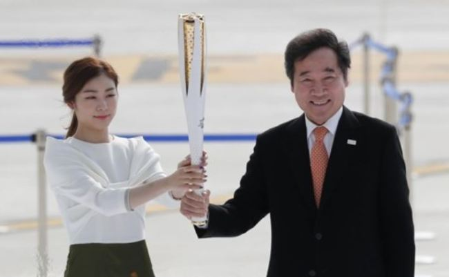 In this file photo taken on Nov. 1, 2017, former Olympic figure skating gold medalist Kim Yu-na (L) and South Korean Prime Minister Lee Nak-yon hold the torch for the 2018 PyeongChang Winter Olympics during the ceremony marking the arrival of the Olympic flame at Incheon International Airport. (Yonhap)