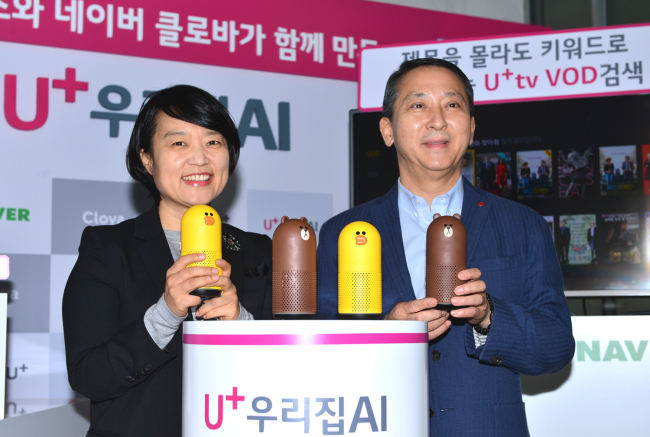 Naver CEO Han Seong-sook (left) and LG Uplus Vice Chairman & CEO Kwon Young-soo hold Friends artificial intelligence speakers at a press conference at the mobile carrier's headquarters in Yongsan, central Seoul, Monday. (LG Uplus)