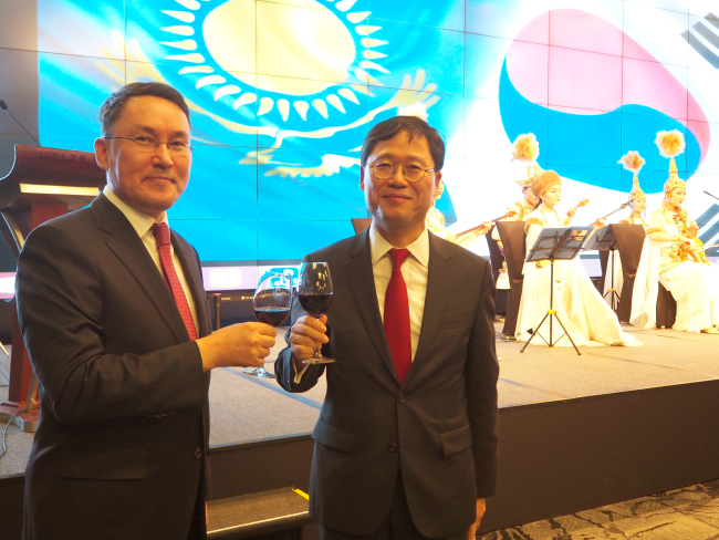 Kazakh Ambassador to Korea Dulat Bakishev (left) and Kim Chang-kyu, deputy minister and standing commissioner for the Ministry of Trade, Industry and Energy, pose at a reception marking Kazakhstan's National Day and silver jubilee of diplomatic relations with Korea in Seoul on Thursday (Joel Lee/The Korea Herald)