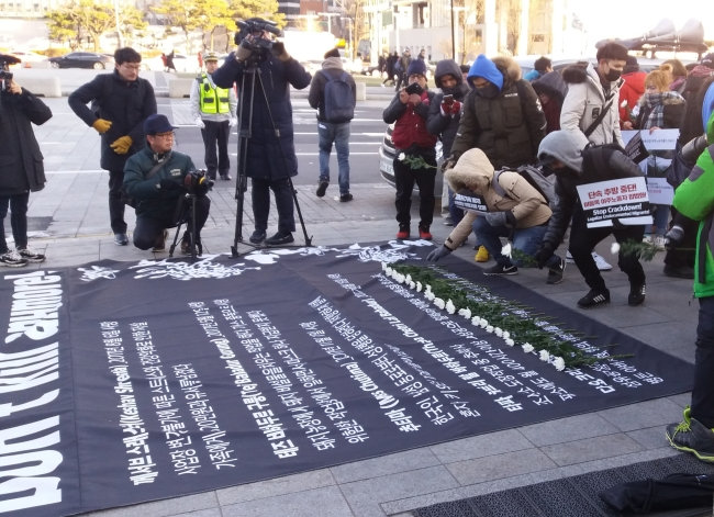 Attendees at the International Migrants Day event in central Seoul lay chrysanthemums on a banner listing the recent deaths of five foreign residents, in Seoul on Sunday. (Paul Kerry/The Korea Herald)