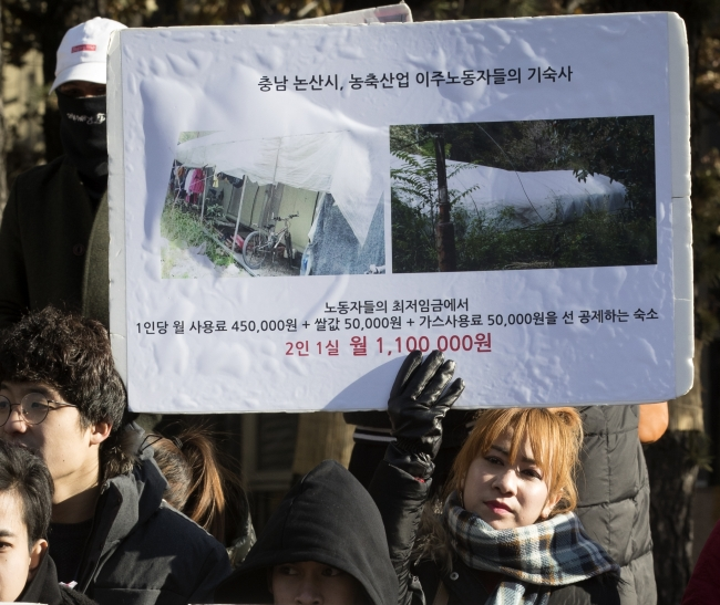 A woman holds up a poster describing living conditions of two migrant workers at the International Migrants Day event in central Seoul. (Yonhap)