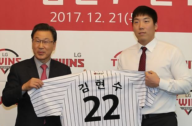 Kim Hyun-soo of the LG Twins (R) and the club president Shin Moon-bum hold up Kim`s new No. 22 jersey during his introductory press conference in Seoul on Dec. 21, 2017. (Yonhap)