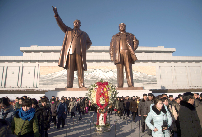 People walk before the statues of late North Korean leaders Kim Il-Sung (left) and Kim Jong-Il after laying flowers to mark the sixth anniversary of the death of the late Kim Jong-Il, at Mansu hill in Pyongyang on Dec. 17, 2017. (AFP/Yonhap)