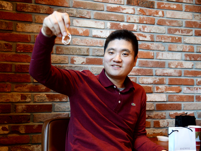Lee Ju-min, CEO of Haesoo.L, holds up products from his brand during an interview with The Korea Herald. (Park Hyun-koo/The Korea Herald)