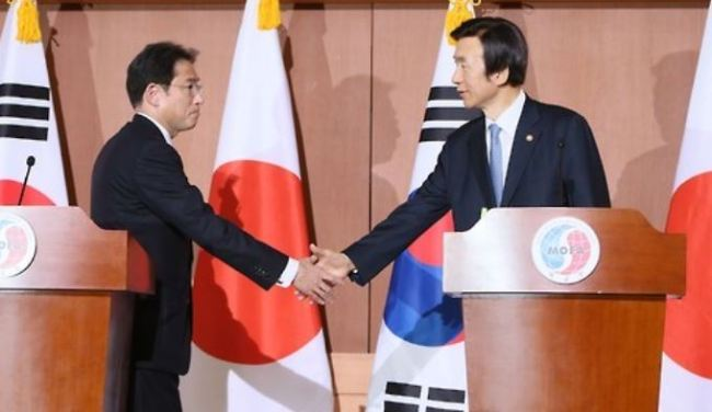 This file photo dated on Dec. 28, 2015, shows then South Korean Foreign Minister Yun Byung-se (R) and Japanese Foreign Minister Fumio Kishida shake hands after announcing an agreement to resolve the issue of Japan`s wartime sexual slaver. (Yonhap)