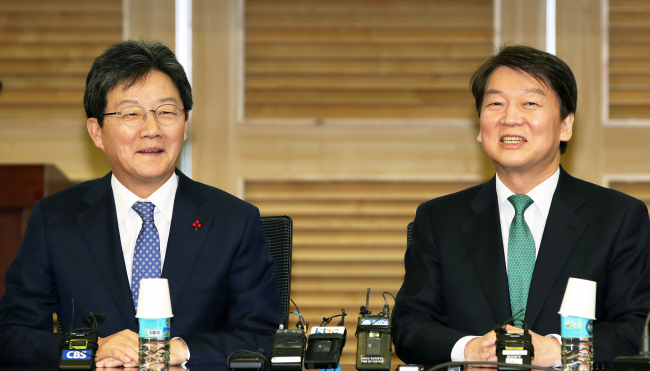 People's Party Chairman Ahn Cheol-soo (right) and Bareun Party Chairman Yoo Seong-min speak at a conference on political merger at the National Assembly on Wednesday. (Yonhap)