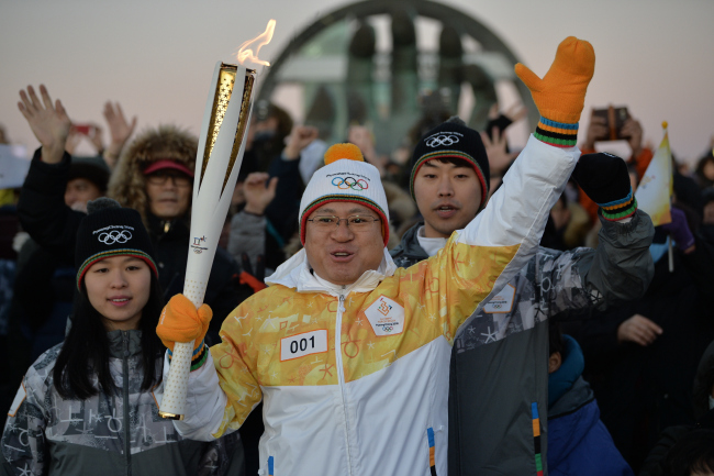 A torchbearer holds up the Olympic torch during a relay for the 2018 PyeongChang Olympic Games on Monday at Homigot Sunrise Square, North Gyeongsang Province. Yonhap