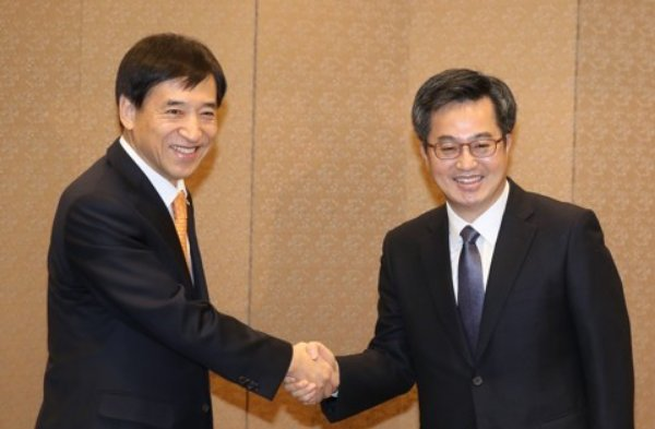 Bank of Korea Gov. Lee Ju-yeol (L) and Finance Minister Kim Dong-yeon shake hands at a breakfast meeting in Seoul on Jan. 4, 2018. (Yonhap)