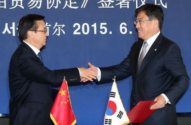 South Korean Trade Minister Yoon Sang-jick (R) and his Chinese counterpart Gao Hucheng shake hands after officially signing a free trade agreement at a Seoul hotel on June 1, 2015. (Yonhap)