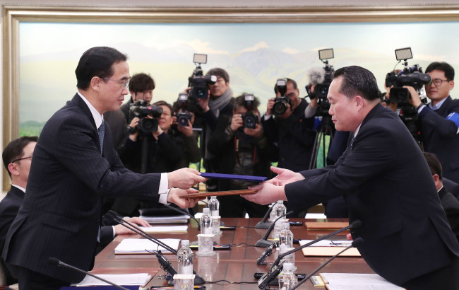 South Korean Unification Minister Cho Myoung-gyon (left)exchanges ajointpress statement with the head of North Korean delegation Ri Son-gwon at their meeting at the Panmunjeom in the DMZ in Paju, South Korea, Tuesday, Jan. 9, 2018. (AP-Yonhap)