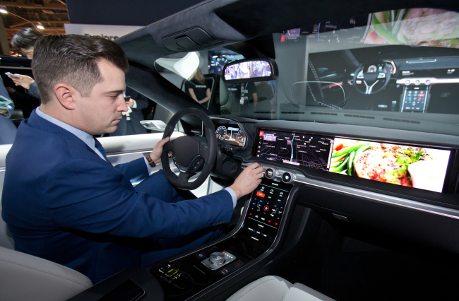 A Samsung Electronics employee demonstrates its advanced automotive platform, digital cockpit, developed jointly with Harman. (Samsung Electronics)