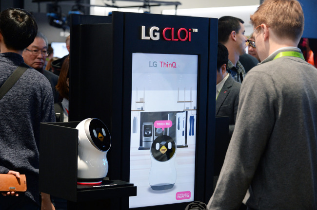 Visitors look at LG's robot brand CLOi on Wednesday at the Consumer Electronics Show in Las Vegas. (LG Electronics)