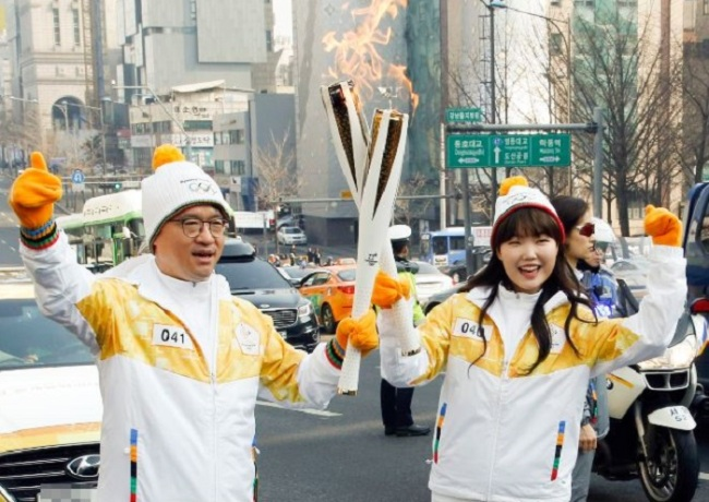 Park Hyun-jong, CEO of BHC Chicken, left, and AKMU`s Lee Su-hyun carries the PyeongChang 2018 Torch in Sinsa-dong, Seoul on Monday. (Yonhap)