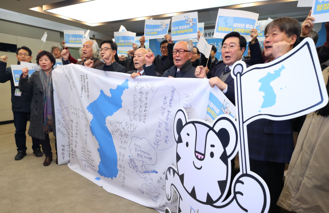 South Korean liberal activists posed alongside Korean Unification flag when they held a press conference Thursday in Seoul to welcome North Korea's participation in the PyeongChang Winter Olympics. Yonhap