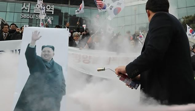 Police extinguish a picture of North Korean leader Kim Jong-un that was set on fire by conservative activist groups during an anti-North Korea rally in front of Seoul Station on Jan. 22, 2018. (Yonhap)