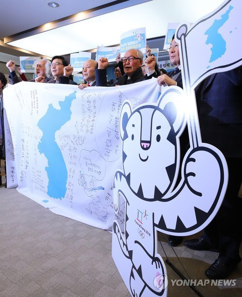 In this file photo, South Korean pro-unification activists hold a Korean Unification Flag, which symbolizes a unified Korea, at Korea Press Center in Seoul on Jan. 11, 2018, after holding a news conference on the push to form a joint inter-Korean cheerleading squad for the Feb. 9-25 PyeongChang Winter Olympics. (Yonhap)