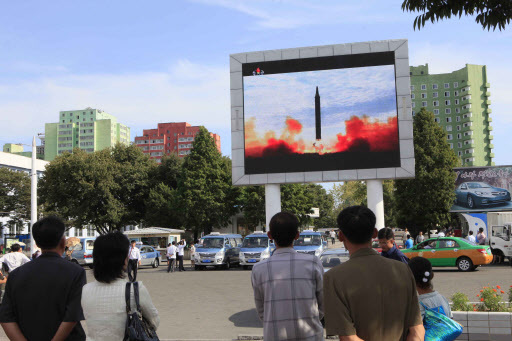 In this Sept. 16, 2017 file photo, people watch the launch of a Hwasong-12 strategic ballistic rocket aired on a public TV screen at the Pyongyang Train Station in Pyongyang, North Korea. (AP-yonhap)