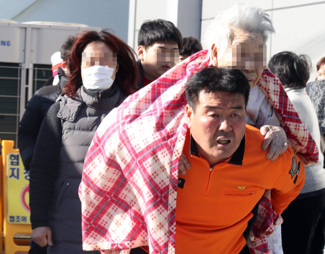A firefighter evacuates patients from the Sejong Hospital in Miryang, South Gyeongsang Province, on Friday morning, after a fire broke out there at 7:30 a.m. (Yonhap)